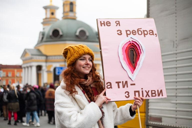 """Учасниця Маршу жінок тримає у руках плакат із написом """"Не я з ребра, а ти - з піхви"""""""