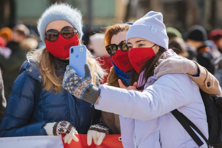 """Учасниці Маршу жінок фотографуються у червоних масках із написом """"Час політики без сексизму"""""""