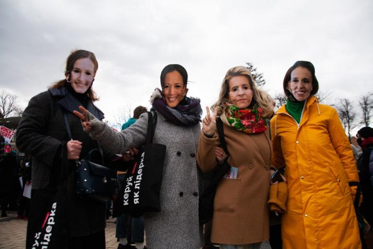 Учасниці Маршу жінок-2021 у масках віцепрезидентки США Камали Гарріс, прем'єрки Нової Зеландії Джасінди Ардерн, очільниці Єврокомісії Урсули фон дер Ляєн та прем'єрки  Фінляндії Санни Марін