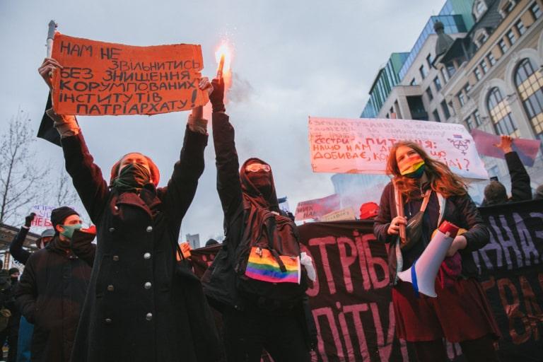 Учасниця Маршу жінок тримає в руках плакат про корумповані інститути патріархату