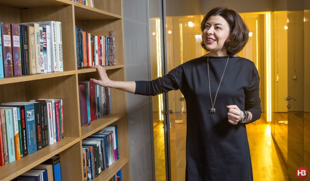 Оксана Сироїд удома біля своєї бібліотеки